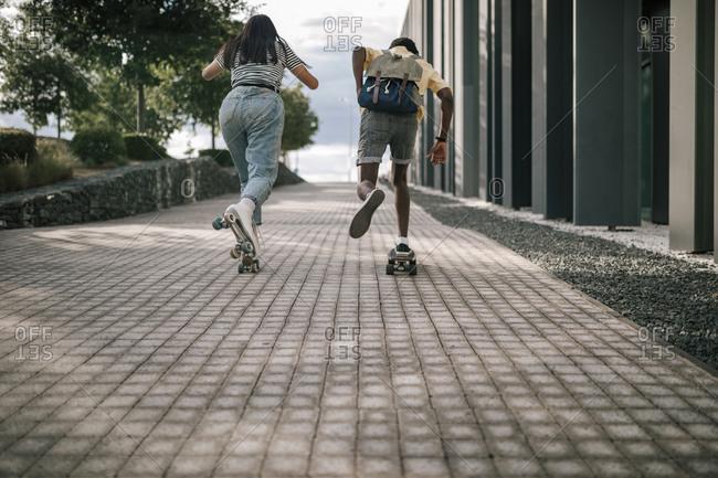 Black boy and white girl skateboarding through the city