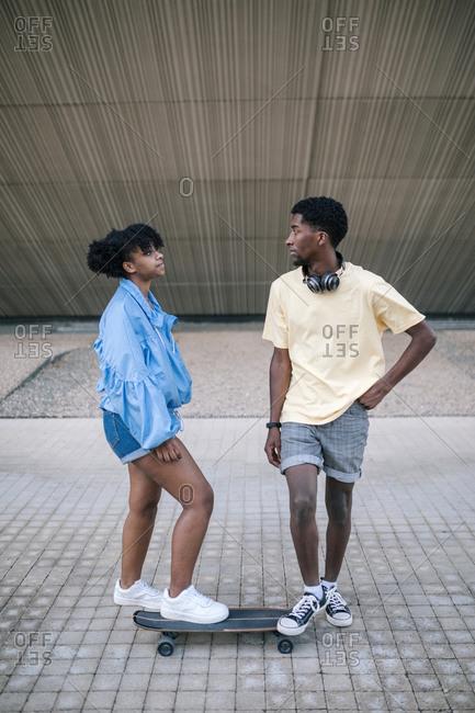 Young black couple skateboarding through the city
