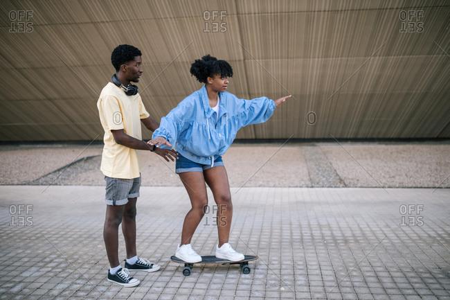 Young black teen teaching girlfriend how to skateboard