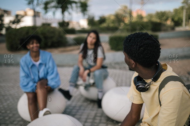 Group of multiracial friends sitting down while skateboarding through the city