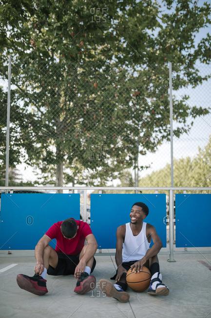 Multiracial teens resting at a basketball game