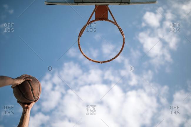Teen boy putting basket into hoop on a basketball court
