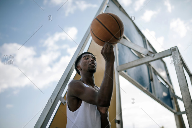 Portrait of young black teenager spinning a basketball on a court
