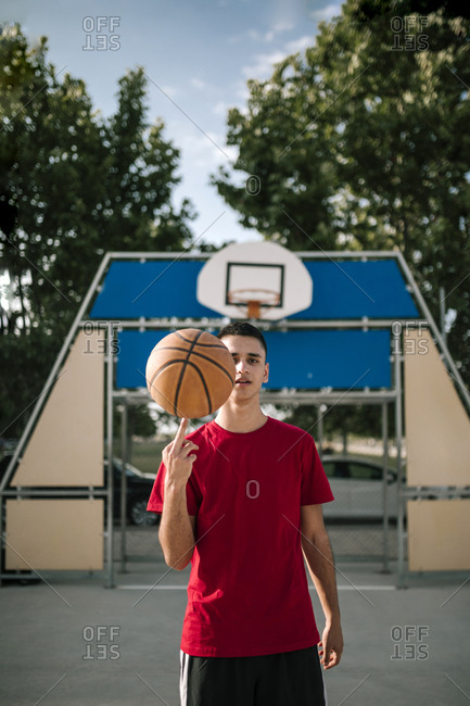 Portrait of young teenage boy spinning a ball on a basketball court