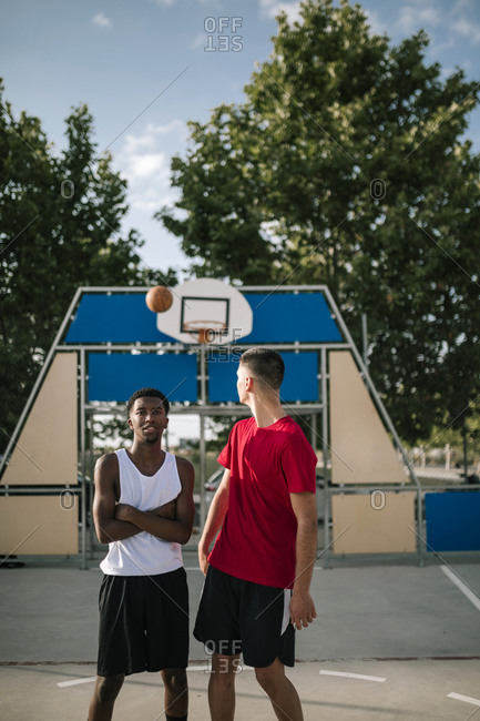 Young multiracial teenagers on a basketball court will ball in the air behind them