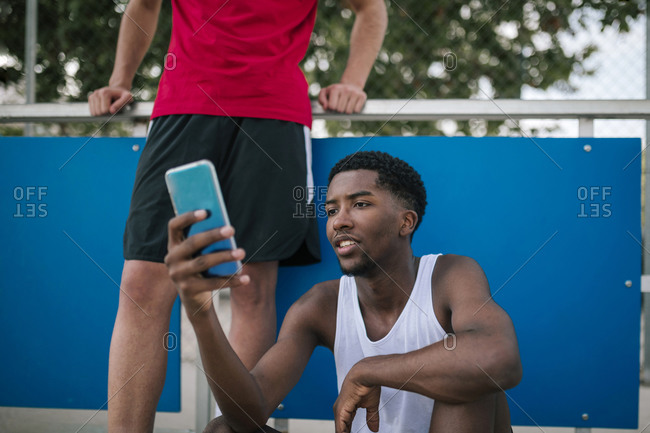 Young multiracial teens using mobile phones at a basketball game