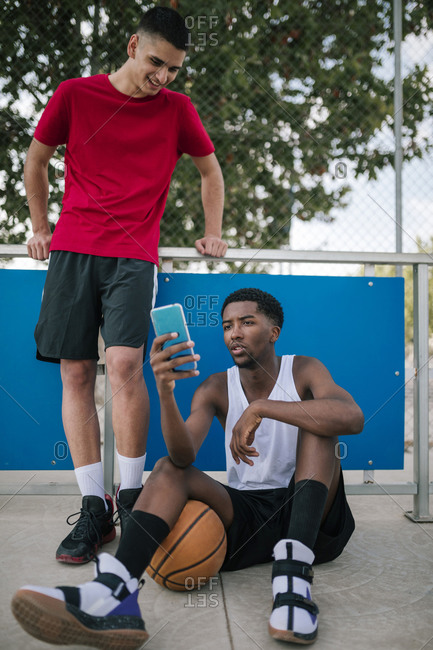 Multiracial teens using mobile phones at a basketball game