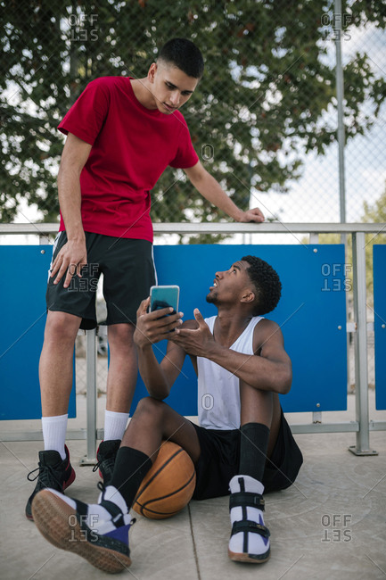 Multiracial teens using mobile phones while taking a break at a basketball game