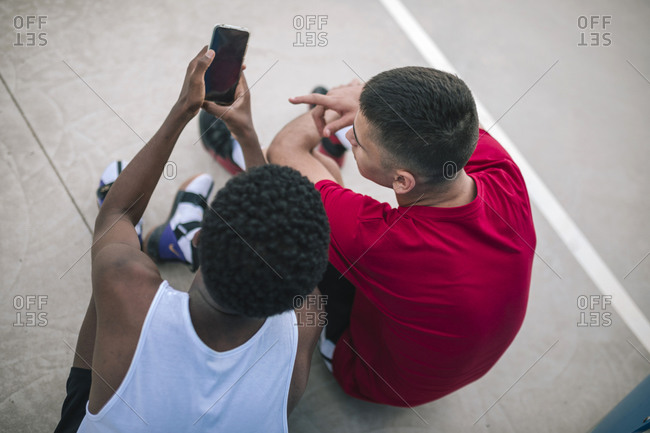 High angle view of multiracial teens using mobile phones at a basketball game