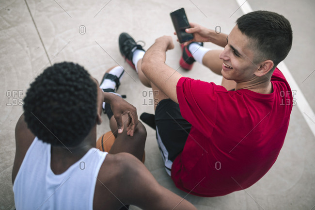 High angle view of multiracial friends using mobile phones at a basketball game