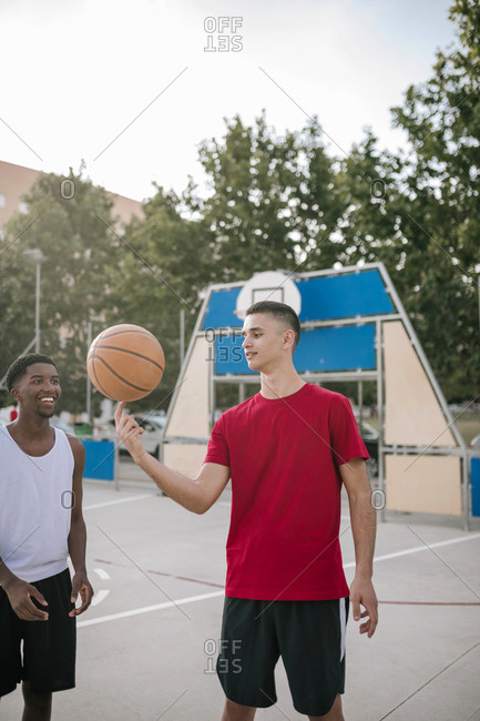 Two young multiracial teens playing basketball with one spinning the ball