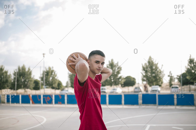 Portrait of young teenage boy holding a ball behind his head on a basketball court