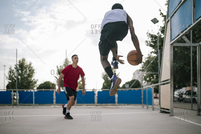 Young multiracial teenagers playing a game of basketball on a court