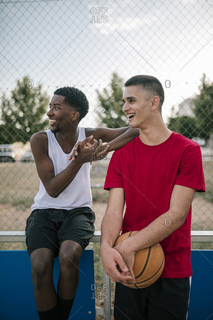 Young teens talking and laughing on a basketball court