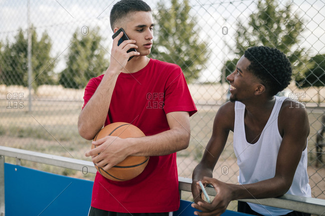 Young multiracial teens with mobile phones at a basketball game