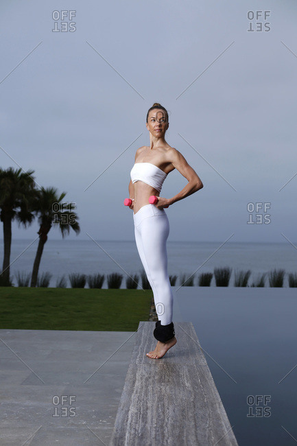 A woman does yoga with weights at sunrise in the La Jolla area of San Diego, California.