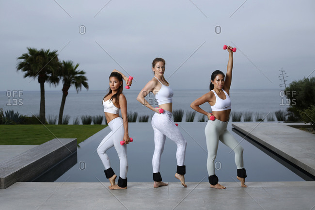 Women do yoga with weights at sunrise in the La Jolla area of San Diego, California.