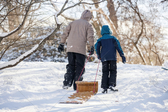 Father and son pulling sled up hill