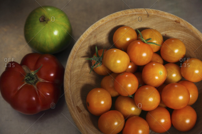 Still life of green zebra, costoluto genovese, and sungold tomatoes in bowl