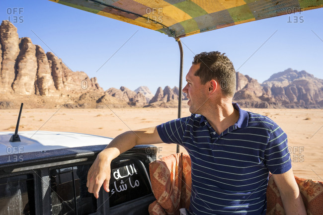 A man rides in the back of a truck through the desert of Wadi Rum in Jordan, mountains in the background.