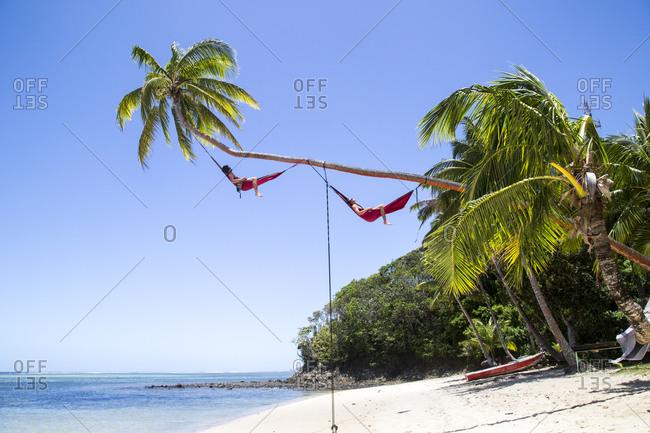 Two men relaxing in hammocks, Koroleva, Fiji