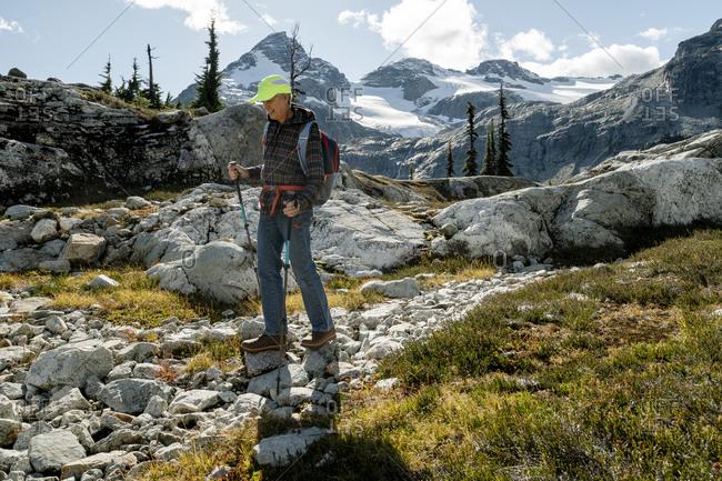 Hiker in alpine meadow, Pemberton, British Columbia, Canada