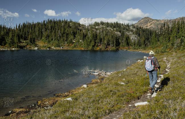 Woman hiking along lakeshore, Pemberton, British Columbia, Canada