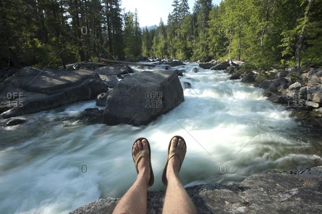 Man sitting by river, Leavenworth, Washington, USA