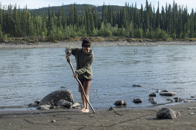 View of woman painting on ground by stick, Yukon, Canada