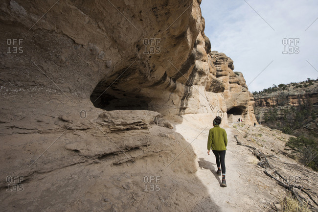 Young woman explores dwellings in canyon, Gila Wilderness, New Mexico, USA