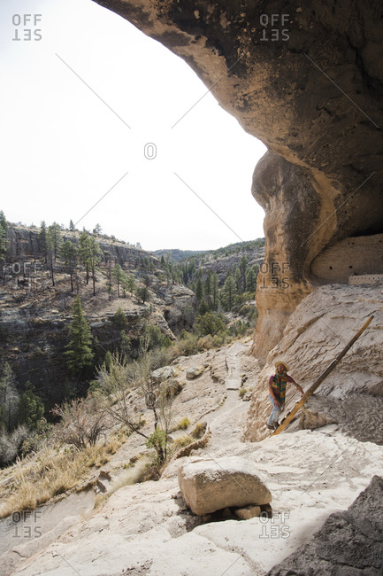 Man explores cliff dwellings, Gila Wilderness, New Mexico, USA