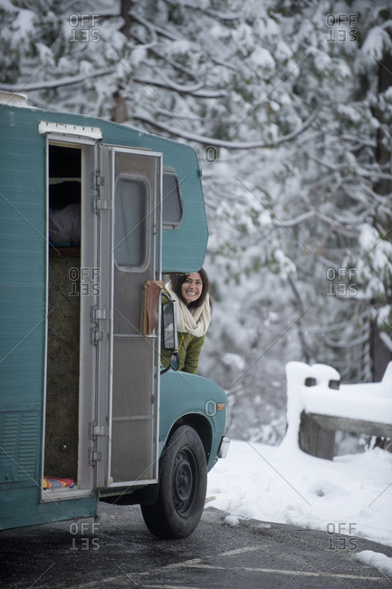 Woman peeking from behind motor home in winter