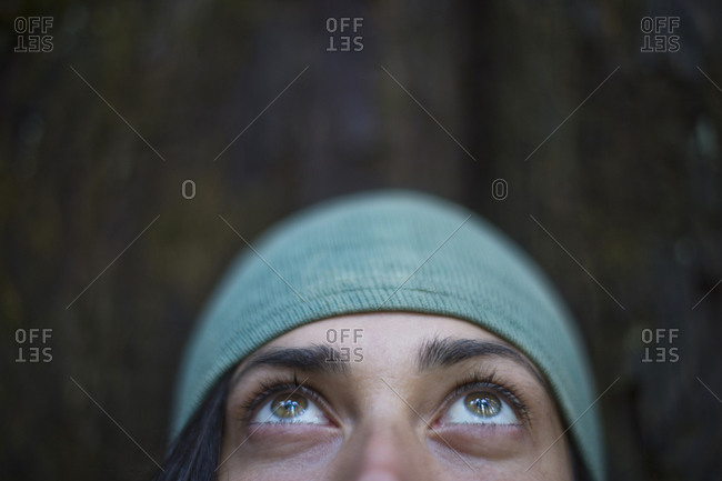 Woman looking up in forest