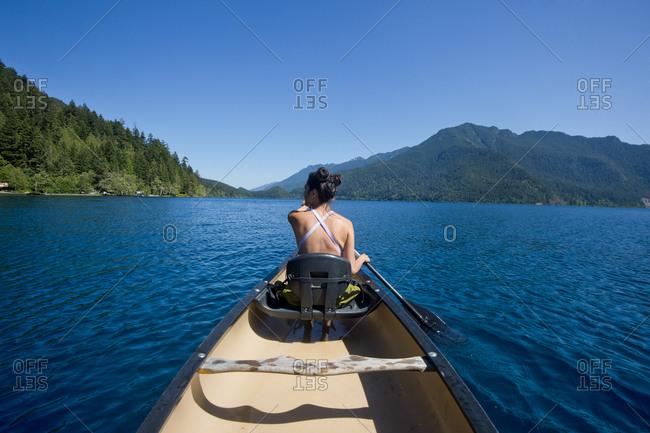 Womack canoeing across blue lake, Olympia, Washington, USA