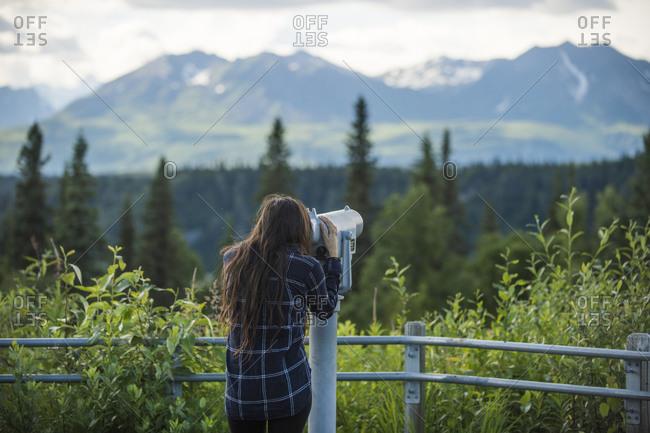 Female hiker using coin-operated binoculars, Alaska, USA