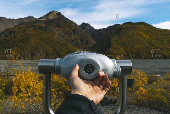 Woman's hand holding binoculars in natural setting, Denali National Park, Alaska, USA