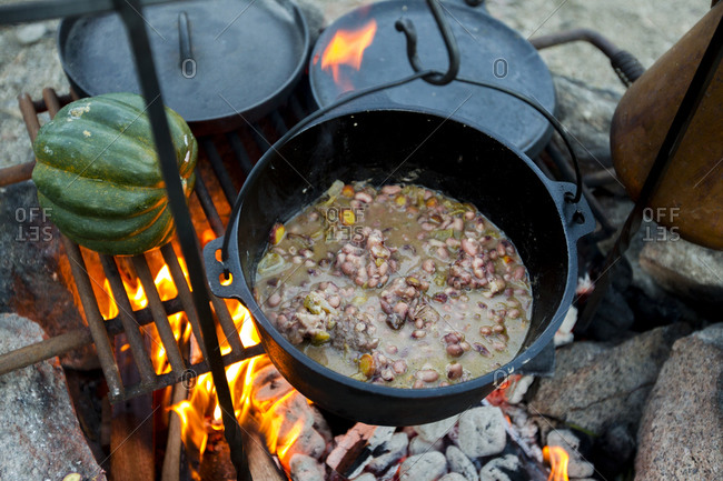 A close up of a cast iron pot cooking vegetables over an open fire.