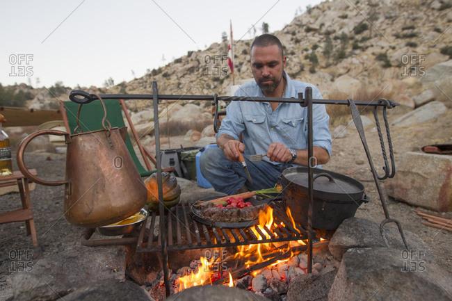 A man cooks dinner over a campfire.