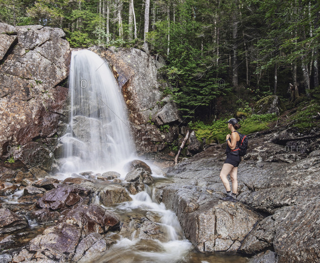 Hiker admiring splashing waterfall, New Hampshire, USA