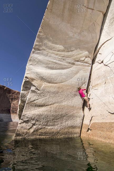 Woman climbing steep cliff, Utah, USA