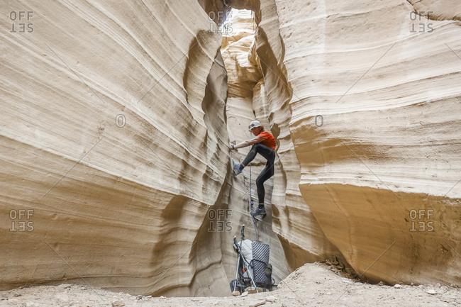 Female hiker climbing in slot canyon, Hayduke Trail, Utah, USA