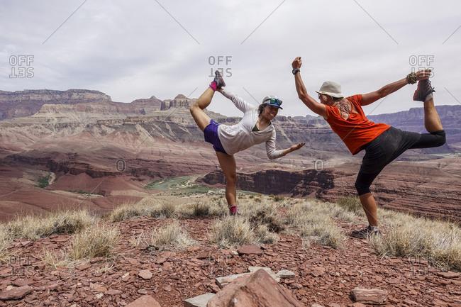 Two female hikers balancing on one leg, Hayduke Trail, Grand Canyon, Arizona, USA
