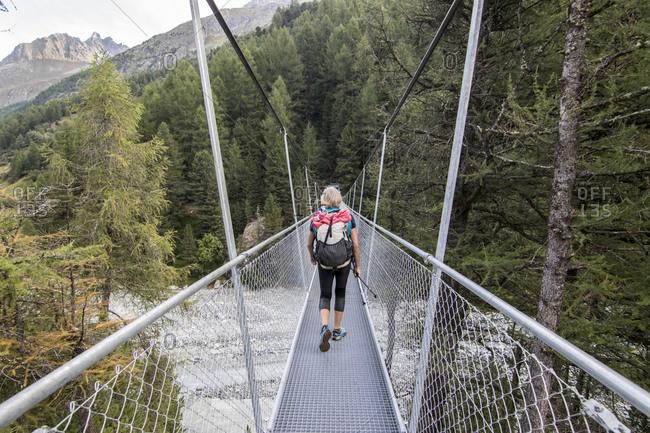 View of woman walking on bridge, Valais, Switzerland