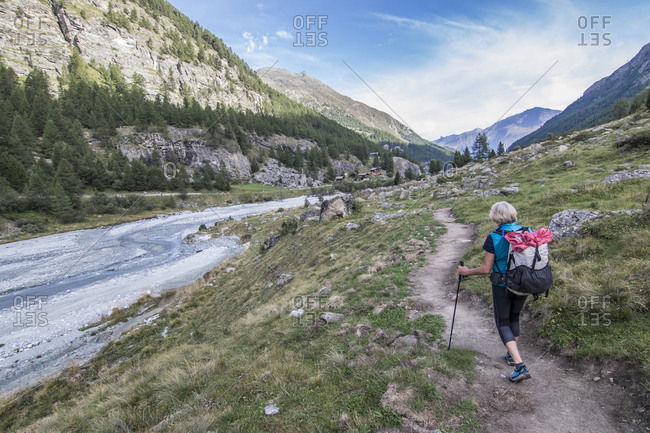View of senior woman hiking by river, Valais, Switzerland