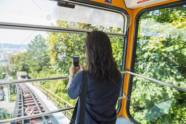 Woman taking smart phone pictures, Zurich, Switzerland