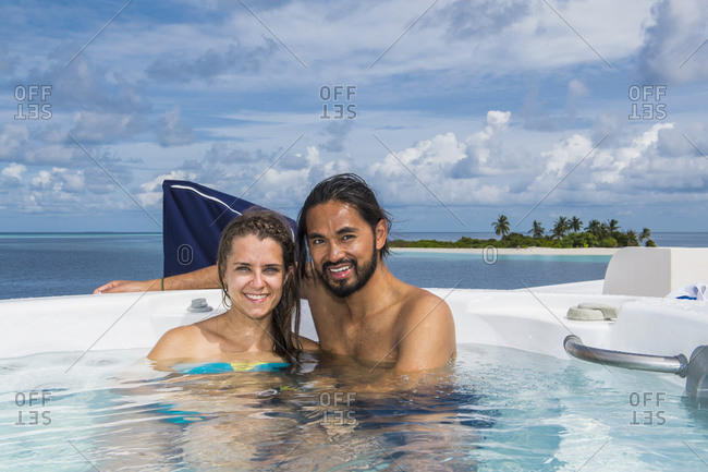 Couple relaxing in hot tub, Maldives