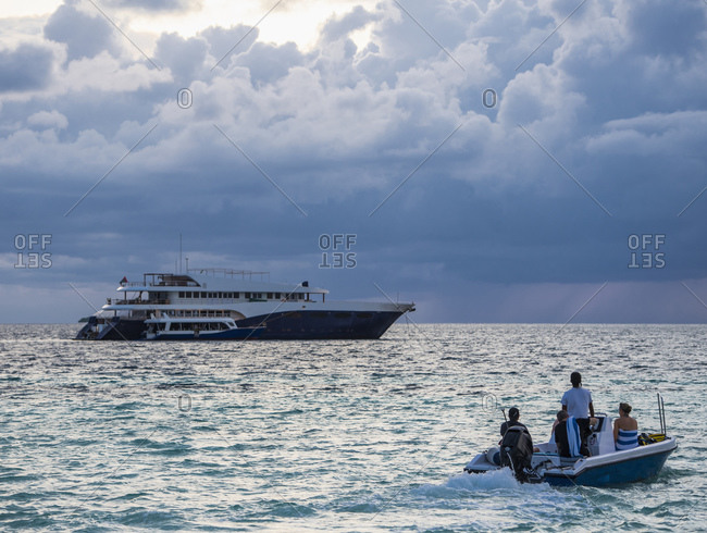 Motorboat transporting passengers to luxurious yacht anchored in Ari Atoll, Maldives