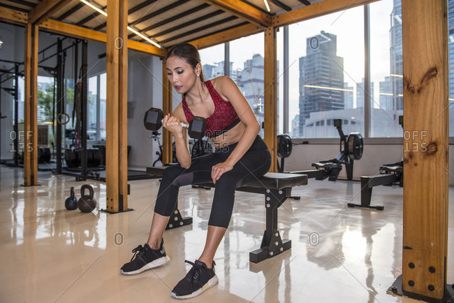 Woman exercising with dumbbell in gym