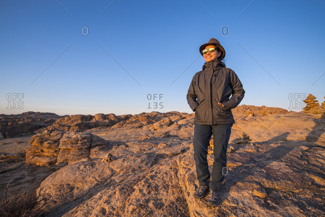 Woman standing in desert, Baga Chula, Gobi Desert, Mongolia