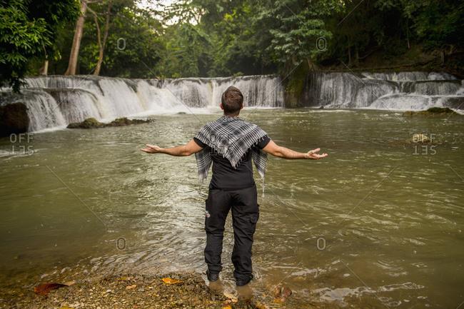 Man standing in front of waterfall, Chet Sao Noi Waterfall National Park, Saraburi Province, Thailand